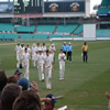 The England team leave the field at the close of play